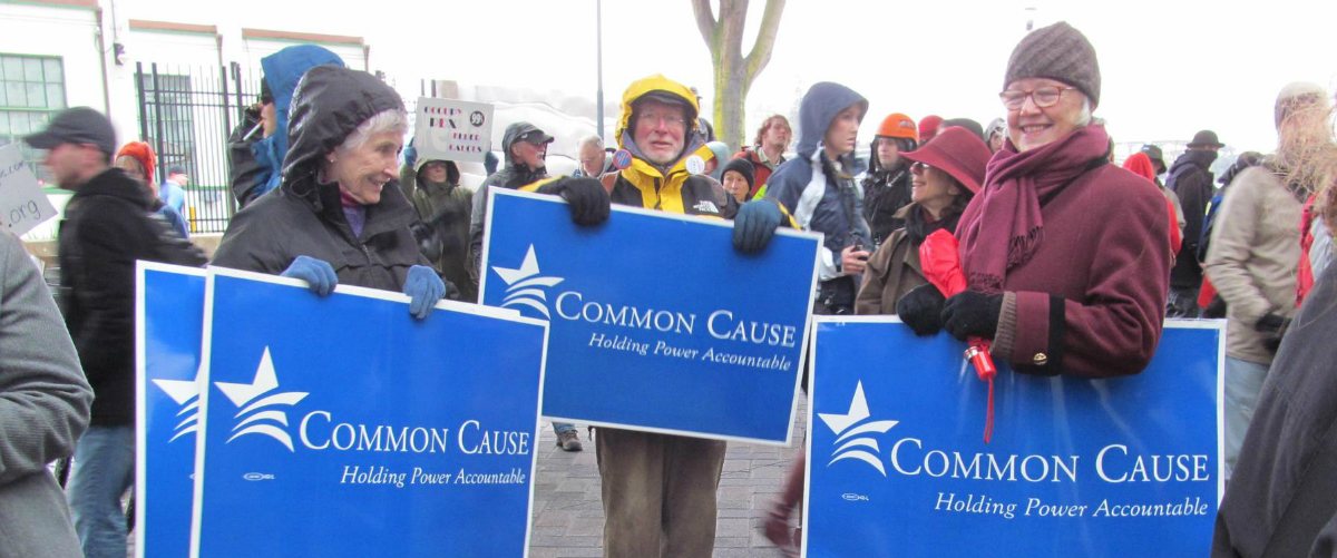 "three people at a protest holding blue signs that say ""Common Cause Oregon"""