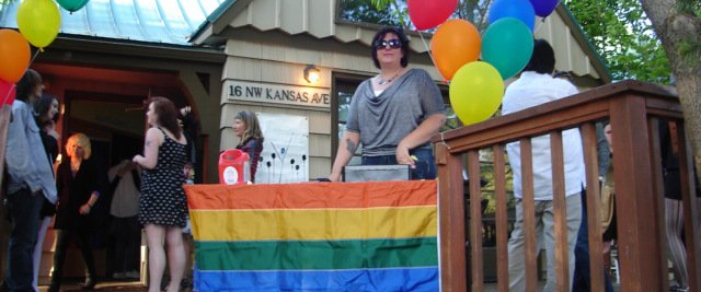 Someone standing at a Human Dignity Coalition with a Pride Flag and rainbow ballongs