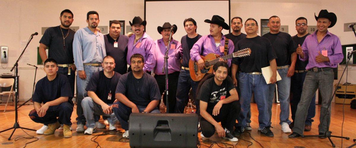 Members of the Latino Club standing with performers on a stage