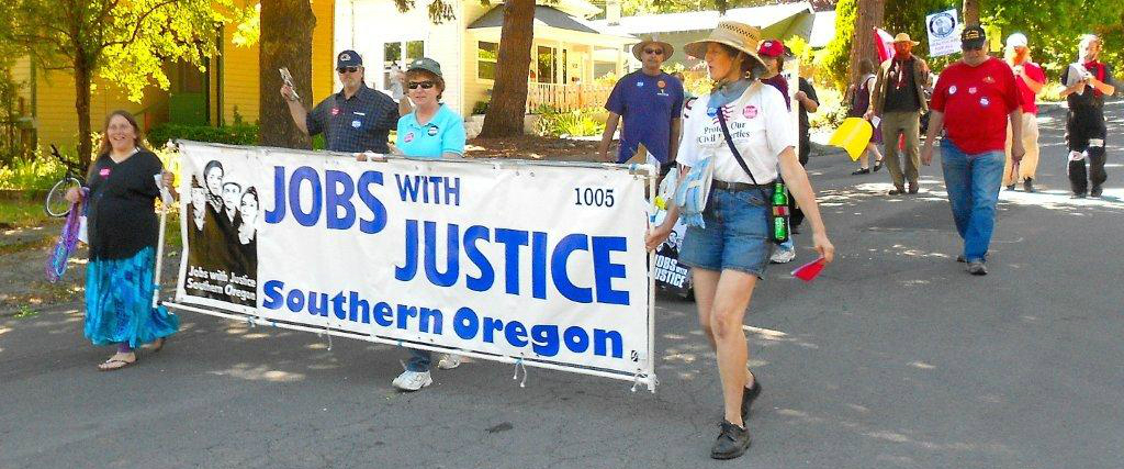 "Adults walking on the street holding a large sign that says ""Jobs with Justice Southern Oregon"""