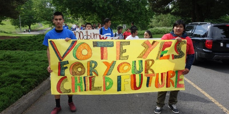 Young activists hold a sign during a protest.