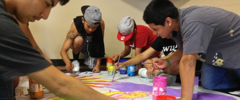Youth from Instituto In Xocitl In Cuicatl painting a mural.