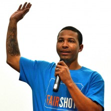 Shaun Franks holds a microphone with his arm raised.