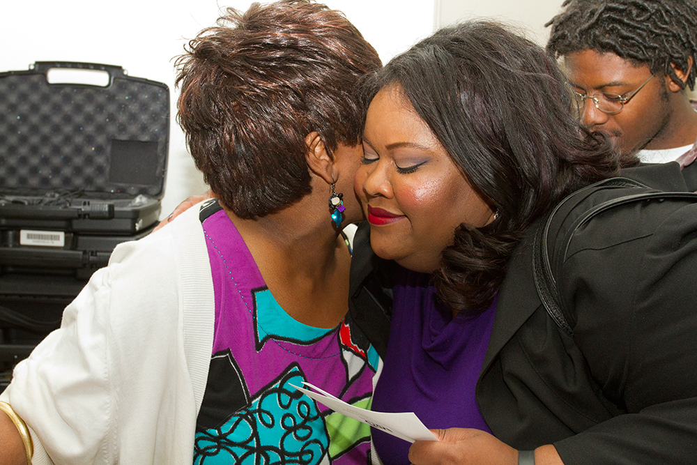Board Chair Sirius Bonner hugs another woman at a Critical Community Conversation