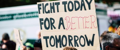 A cardboard sign above a crowd that reads Fight Today for a Better Tomorrow.