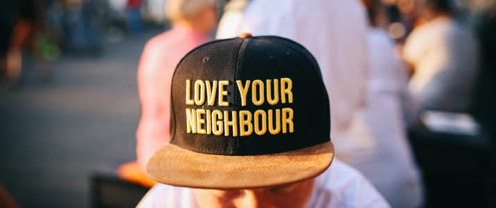 Picture of a person wearing a hat that reads: Love Your Neighbor