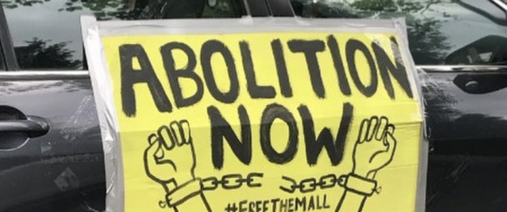 Protest sign taped to a car that reads: Abolition Now